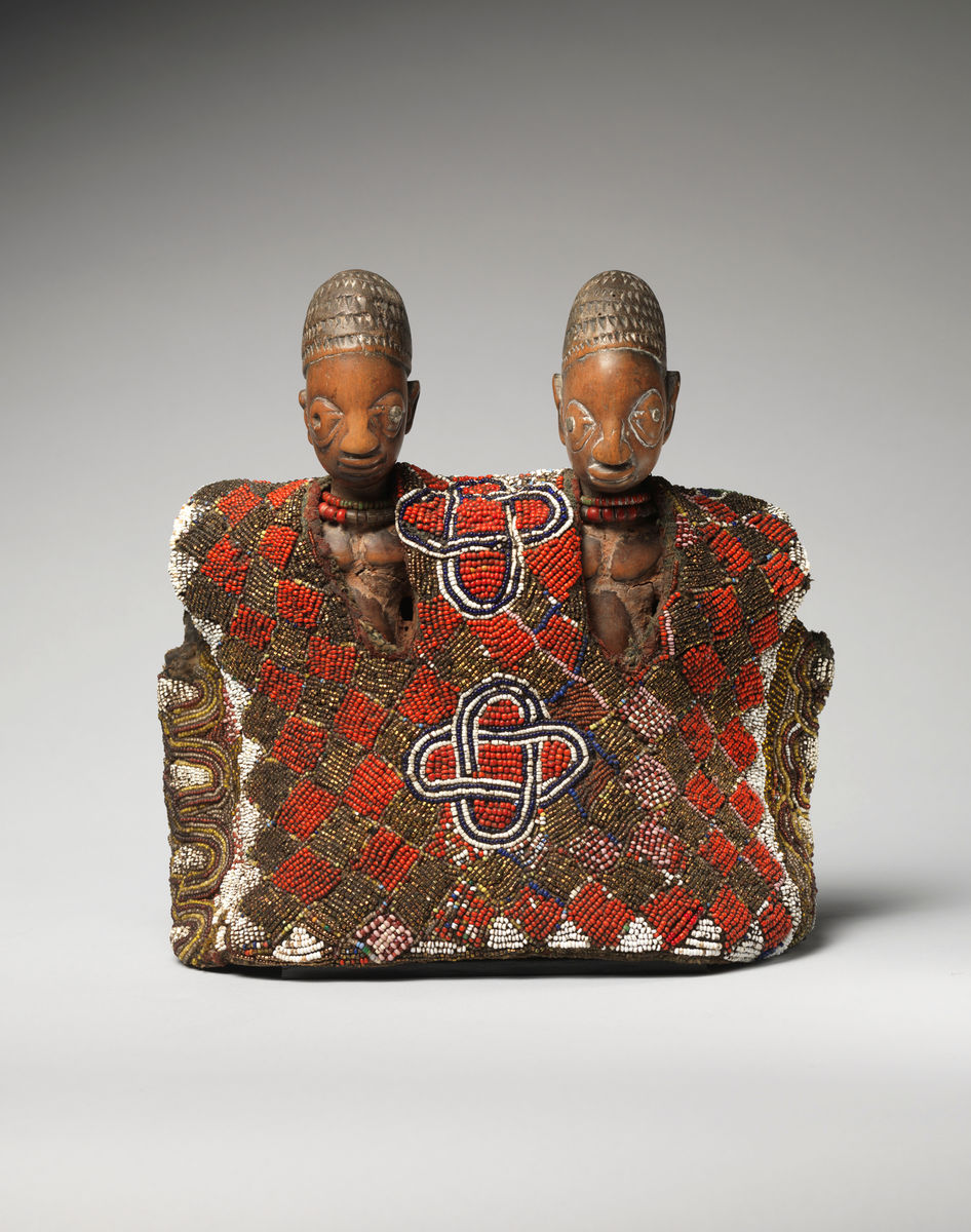 Yorùbá artist, Twin commemorative figures (ere ibeji) with tunic, late 19th–early 20th century. Wood, tukula, metal, glass beads, cotton, abrus seeds, and leather. Museum purchase, Fowler McCormick, Class of 1921, Fund. Photo Bruce M. White.