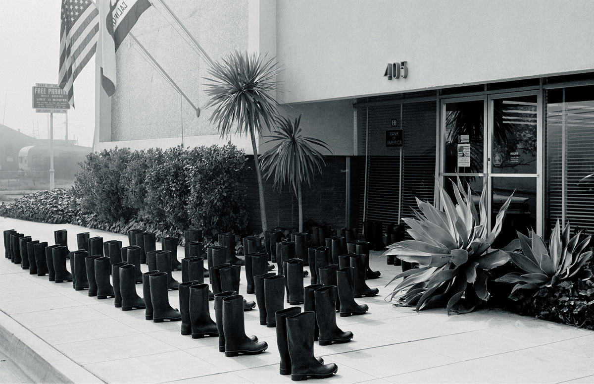 Eleanor Antin (born 1935, Bronx, NY; active San Diego), photographs by Philip Steinmetz American, 1944–2013), 100 Boots at the Bank, from the series 100 Boots, a set of 51 photo-postcards, 1971. Postcard. Museum purchase, Fowler McCormick, Class of 1921, Fund. © Eleanor Antin / Courtesy of Richard Saltoun Gallery, London