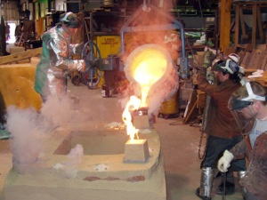 Pouring the molten bronze down the pour cup into the hollow cavity.