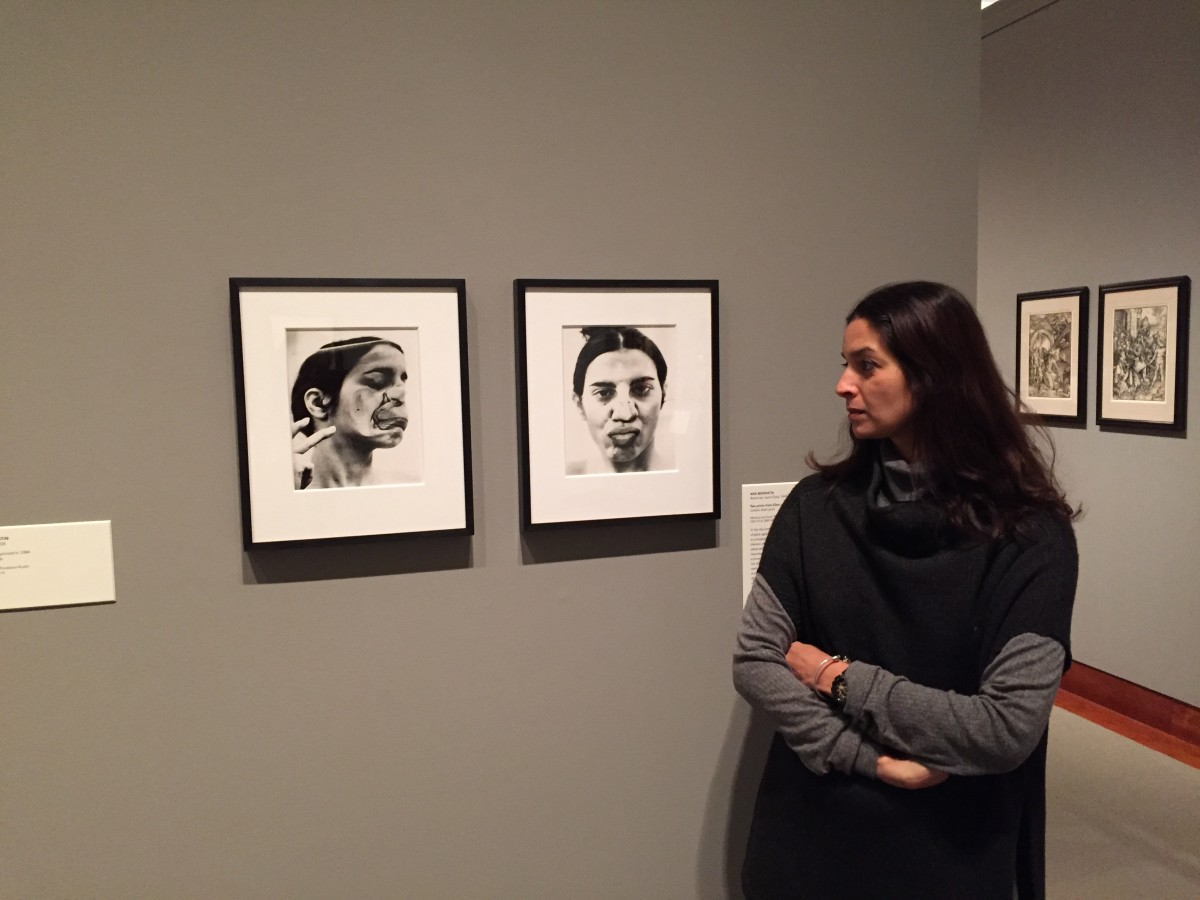 Jhumpa Lahiri in the Art Museum galleries alongside two prints from Ana Mendieta's Untitled (Glass on Body Imprints–Face), 1972