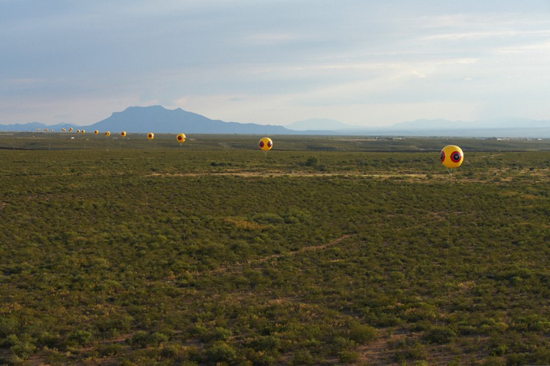 Postcommodity, <em>Repellent Fence</em>, 2015. Land art installation and community engagement (Earth, cinder block, para-cord, pvc spheres, helium). Installation view, US/Mexico Border, Douglas, Arizona / Agua Prieta, Sonora. © Postcommodity 2015
