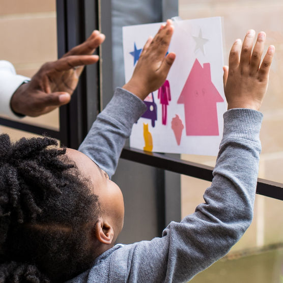 Child taping art project to a window.
