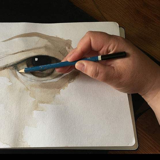 Hand of artist holding pencil brush over drawing.