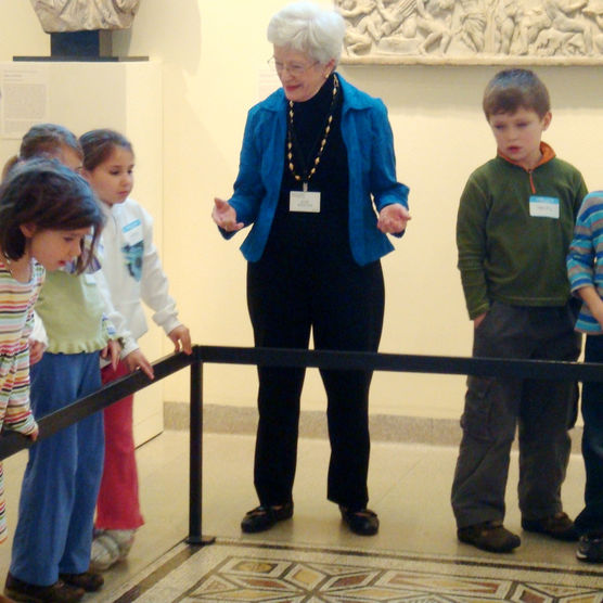 Docent explaining exhibit to group of children