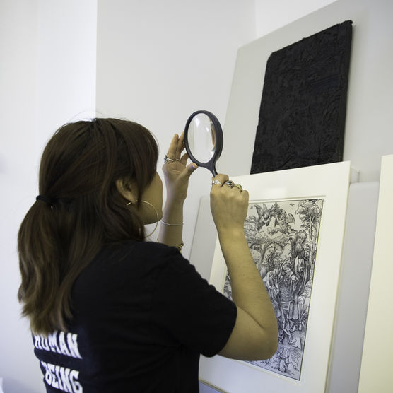 McCrindle intern examines work in the collection with a magnifying glass