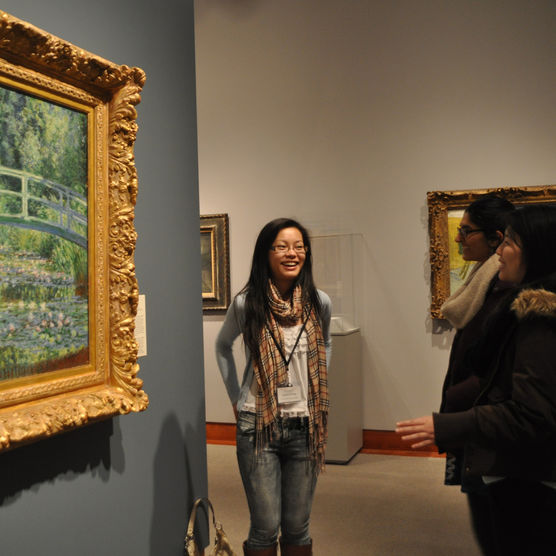 Student volunteers tours paintings in the museum