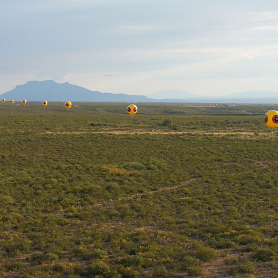 Postcommodity, <em>Repellent Fence<em>, 2015. Land art installation and community engagement (Earth, cinder block, para-cord, pvc spheres, helium). Installation view, US/Mexico Border, Douglas, Arizona / Agua Prieta, Sonora. © Postcommodity 2015