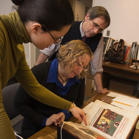 Faculty looking over book on desk